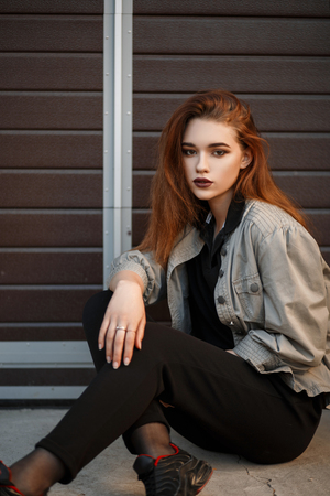 Beautiful young model woman in fashionable jacket and black T-shirt with pants sitting on the street near the gate Reklamní fotografie