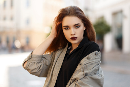 Fashion portrait of a beautiful young woman with makeup in a stylish jacket and fashionable shirt posing on the street