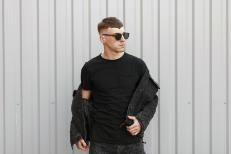 Handsome young stylish man with sunglasses in a denim fashion jacket and a black t-shirt poses near the gray wall Foto de archivo