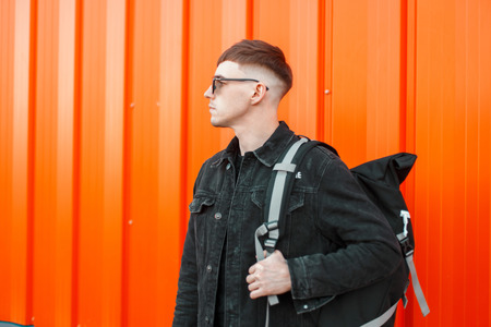 Stylish handsome young man with a hairstyle in sunglasses in fashionable black clothes with a bag stands near the orange wall