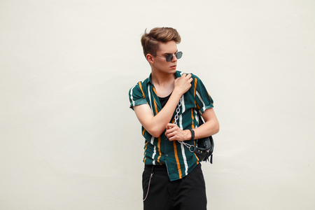 Young handsome guy in fashion beach clothes with a bag near the green wall