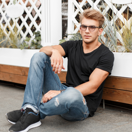 Stylish handsome model with a hairstyle with glasses in a black T-shirt and jeans sitting near a wooden fence on the street Stock Photo