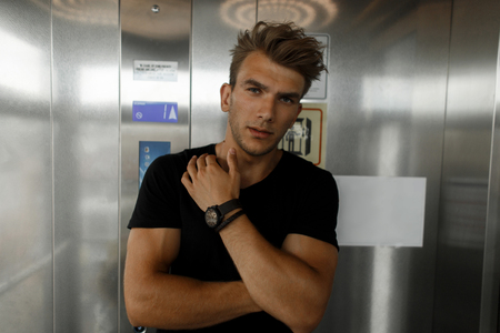Young handsome stylish man with a hairstyle in a black fashionable T-shirt in the elevator Stockfoto