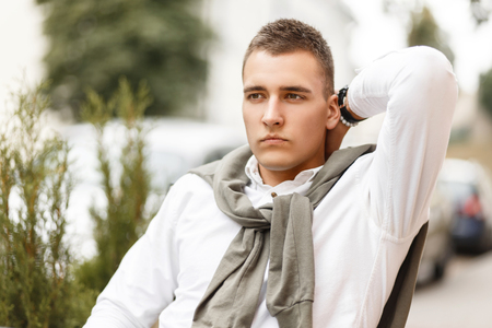 Stylish handsome young millionaire man in white shirt with sweater sitting in the city Фото со стока