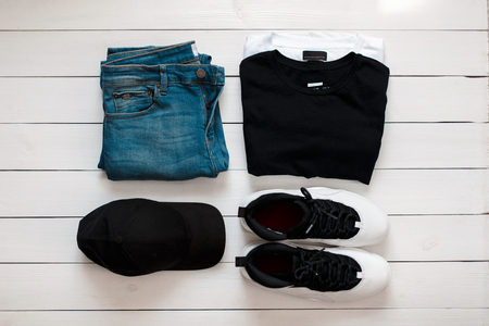 Set of fashionable clothes on the table. Jeans pants, T-shirts, white stylish leather sneakers and a cap lie on a wooden white floor. View from above