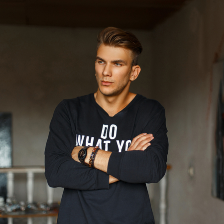 Handsome stylish young man in a black pullover with white text posing indoors Archivio Fotografico - 106447956