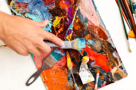 mans hand with a paint brush paints with oil paints Stockfoto