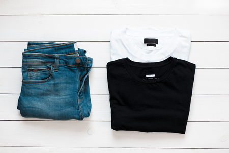 Summer mens clothing style. Jeans with a black and white T-shirt lie on a white wooden table