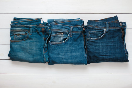 Fashionable blue stylish jeans lie on a white wooden table. View from above Stock Photo