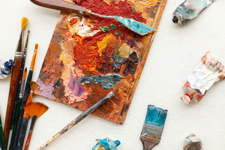 Vintage brushes with oil paint lie on the desktop. A set of tools for the artist Zdjęcie Seryjne