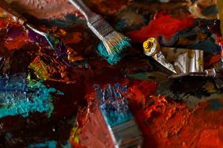 Bright colorful abstract background from oil paint with artist tools