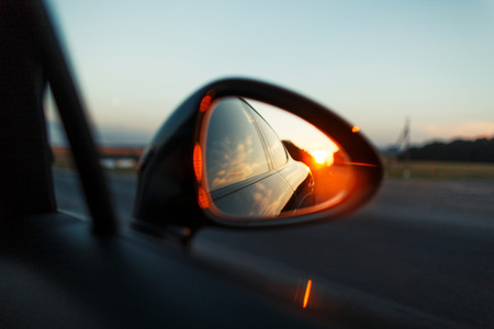 Travel by car with a sunset in the mirror