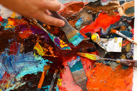 set of an artists tool on a background with oil paint. Mans hand draws with a brush