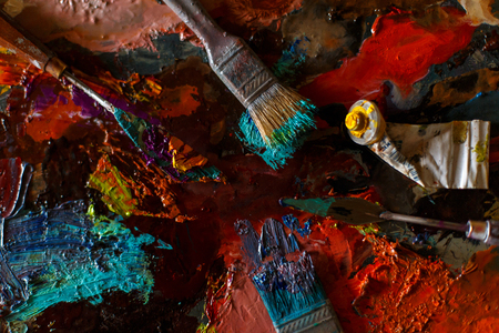set of artist, brushes and oil paint on a colorful abstract background