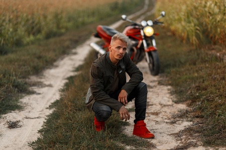 Handsome stylish hipster man in a fashion khaki jacket with red shoes is sitting near a motorcycle in a cornfield. Traveling by nature