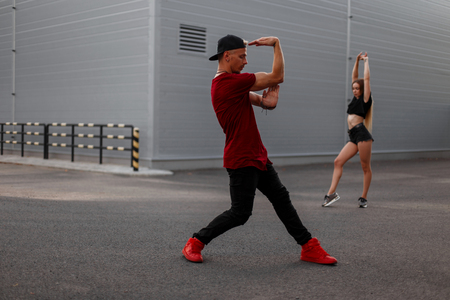 Stylish handsome hip-hop dancer in fashionable clothes with a cap dancing on the street. Sexy girl dancer on the background Banque d'images - 107590119