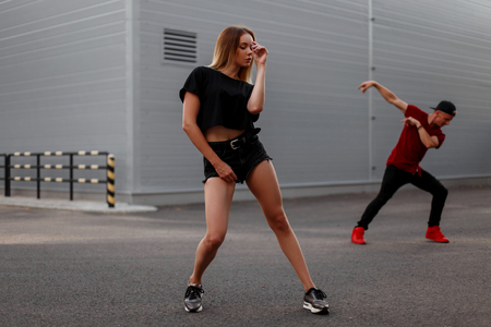 Stylish beautiful young hip-hop woman dancer with black fashion clothes dancing outside. Dancer man on the background Stock Photo