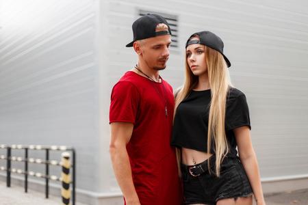Hermosa pareja elegante en ropa casual de moda con gorras en la calle