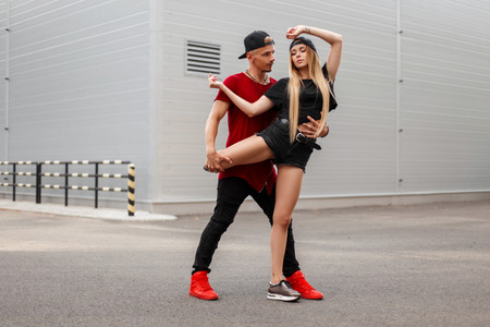 Handsome man with a beautiful young girl dancing breakdance on the street. Street dance Banque d'images - 107591056