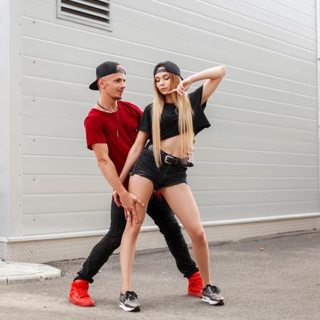 Piękna stylowa młoda para w modne ubrania z czapką taniec na ulicy. Zdjęcie Seryjne