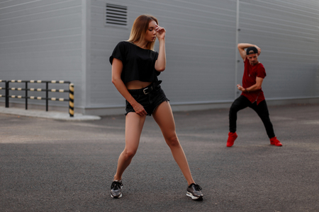 Sexy beautiful young girl dancer in black T-shirt with shorts dancing on the street. Male dancer on the background Banque d'images - 107590929