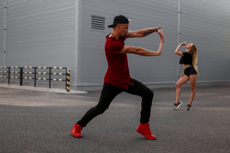 Handsome young man dancer with a baseball cap in a red tank top, black jeans and red shoes is dancing on the street. Woman dancer on background