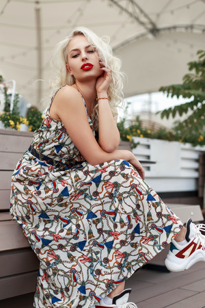 Fashionable young model woman with red lips in a stylish dress with a pattern with shoes sitting on a wooden bench in the city Imagens