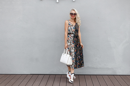 Beautiful young woman model with sunglasses with stylish white bag and fashionable dress with patterns stands near the gray wall