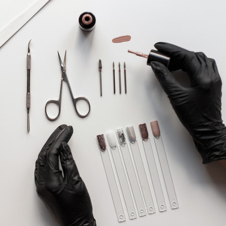 Nail care. A set of tools for manicure. Female hands in black gloves make manicure