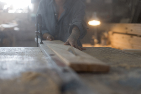 Female hands saw the wooden product on the saw in the workshop. The concept of women's handwork