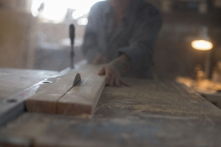 Strong woman saws a wooden product on a saw machine in the workshop