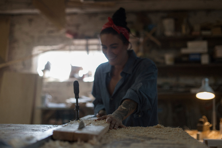 Happy woman working in the workshop, sawing a wooden product. Handmade concept Banque d'images