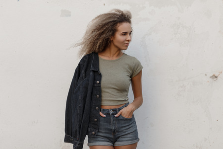 Sexy beautiful young model woman with curly hair in a t-shirt and jeans shorts with jacket posing near white wall