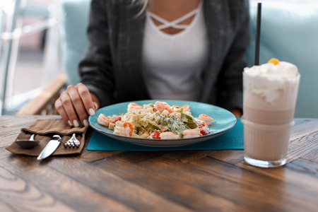 Young woman eats a Caesar salad and drinks a milkshake at a restaurant
