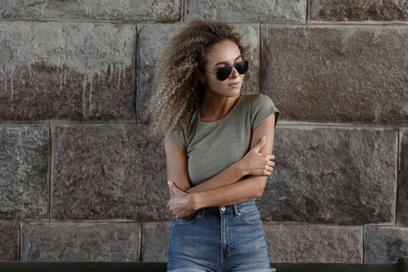 Fashionable young curly girl with stylish sunglasses in a casual clothes on the street near the stone wall