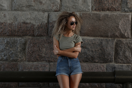 Stylish beautiful young woman model with curly hairstyle and sunglasses in jeans shorts and a fashionable t-shirt near a stone wall on the street