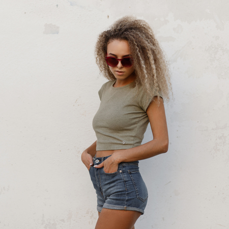 Stylish sexy young beautiful curly girl with sunglasses in a fashion T-shirt and jeans clothes shorts stands near the white wall