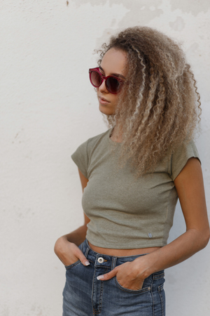 Young beautiful cute curly model woman with sunglasses in a t-shirt and denim fashionable clothes near a white wall Stock fotó - 109394163