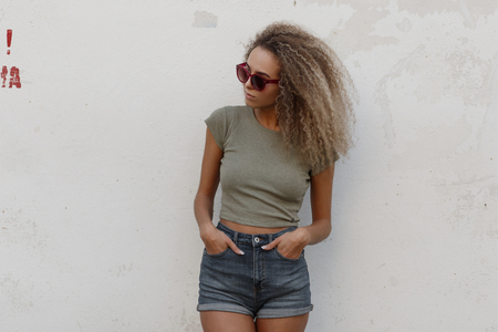 Fashionable beautiful young sexy model woman with curly hair in a T-shirt and denim stylish shorts stands near a white wall on the street