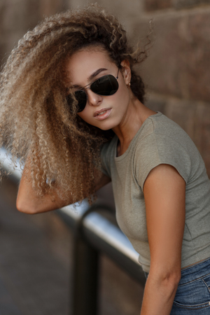 Young beautiful stylish curly woman with trendy sunglasses in a fashion t-shirt on the street Stock fotó