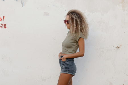 Sexy beautiful young model woman with curly hair in a fashion t-shirt and jeans shorts near a white wall on the beach