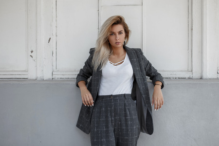 Beautiful stylish woman in a fashionable gray business suit stands near a wall in the street. Business Fashion Lady