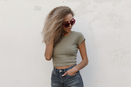 Stylish beautiful young curly woman with pink sunglasses in vintage jeans clothes and a stylish t-shirt near the white wall Stock fotó