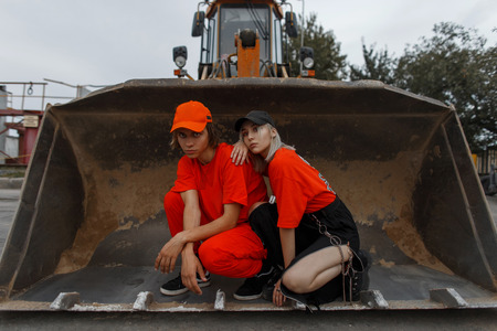 Stylish young couple in trendy orange clothes with cap sitting in a bucket of a construction vehicle