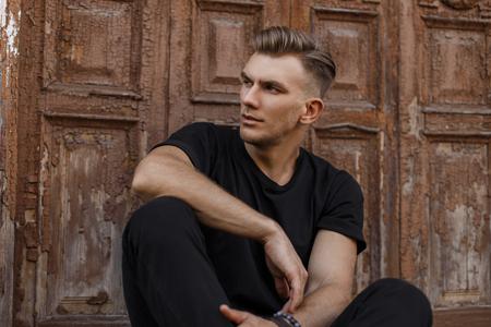 Hübscher junger amerikanischer Modellmann mit Frisur in schwarzem trendigem T-Shirt, der in der Nähe einer Vintage-Holztür sitzt Standard-Bild