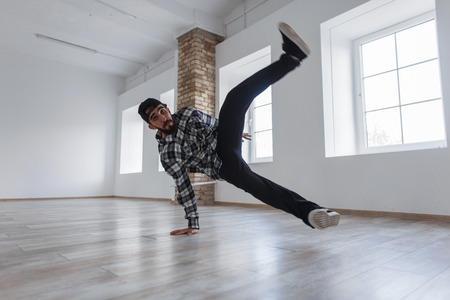 Handsome young man dancer with a cap in casual clothes dancing break dance in studio