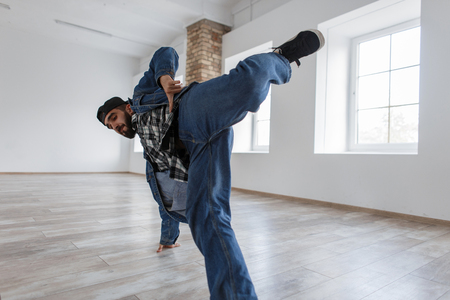 Handsome young stylish man with a cap in a denim jacket and jeans with sneakers dancing in a dance studio Stock Photo
