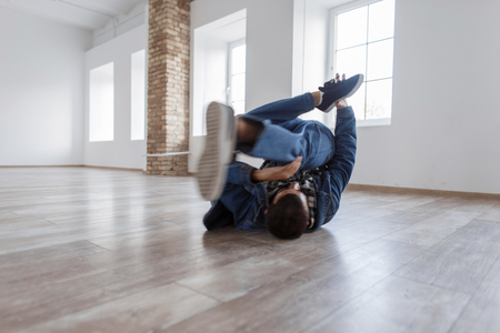 Young male dancer in fashionable denim dress dancing in studio on the floor Фото со стока