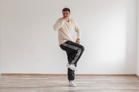 Young funny guy dancer shows his skills standing on his leg in a white modern studio
