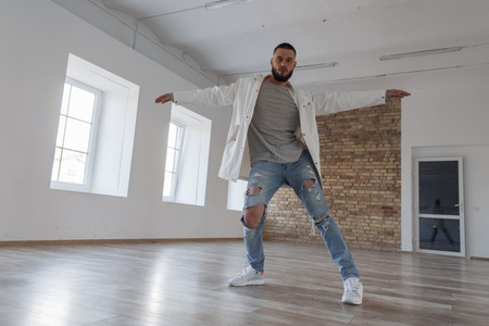 Fashionable handsome young stylish man dancer in jacket and ripped jeans dancing in dance studio